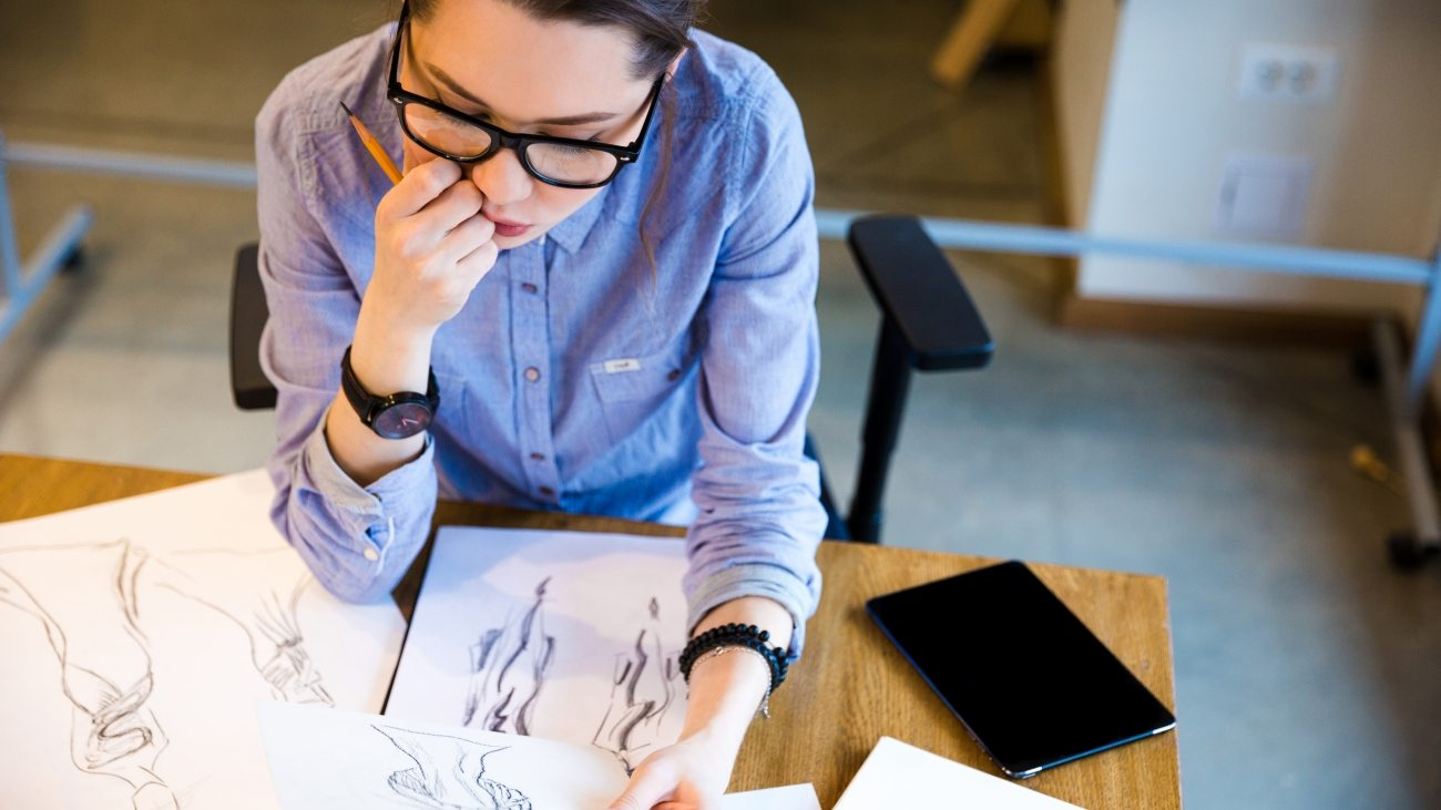 Top view of pensive pretty young woman fashion designer sitting on workplace and looking at sketches