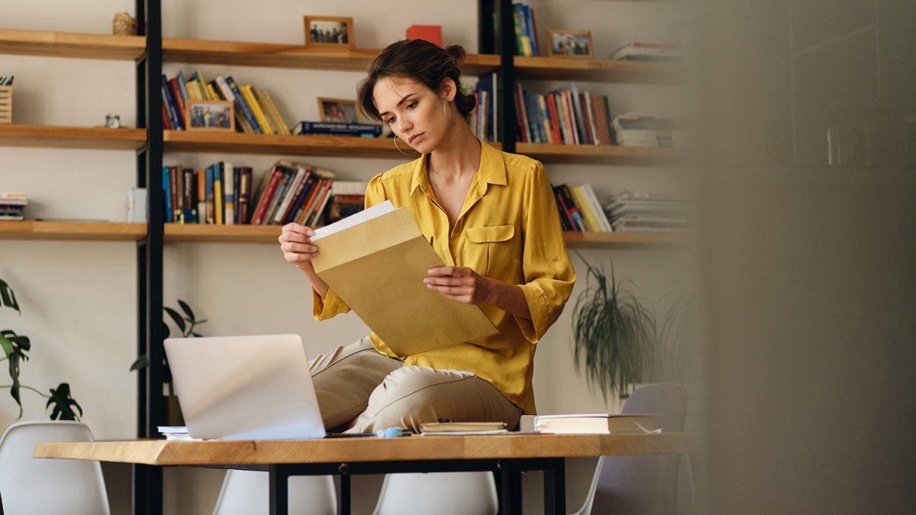 beautiful-woman-in-shirt-sitting-on-desk-with-LE96BAG