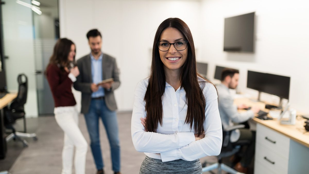 portrait-of-young-businesswoman-posing-in-office-WEU5FBG
