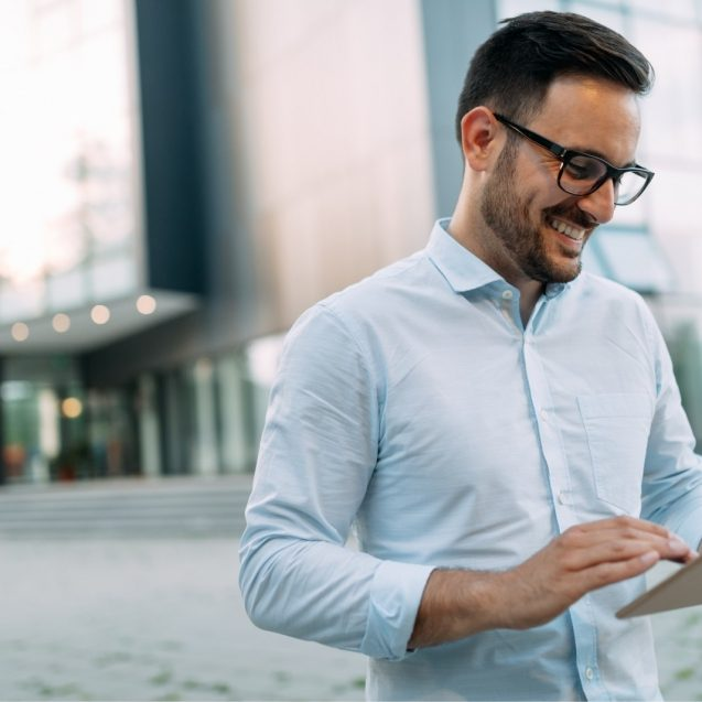 portrait-of-businessman-in-glasses-holding-tablet-AWVHCJU