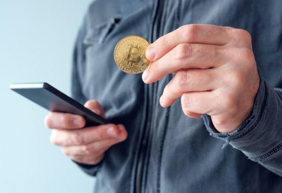 man-with-bitcoin-and-mobile-phone-P8NS7Y4