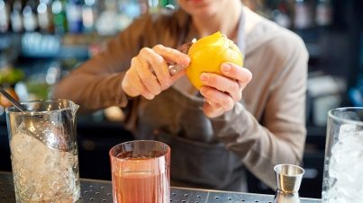 bartender-peels-orange-peel-for-cocktail-at-bar-P97775Y