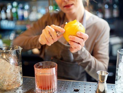 bartender-peels-orange-peel-for-cocktail-at-bar-P97775Y