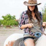 beautiful-young-woman-cowgirl-sitting-and-riding-P3DWVG6