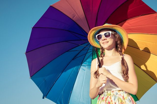 teen-girl-with-umbrella-standing-on-the-beach-at-PMEQ6S8