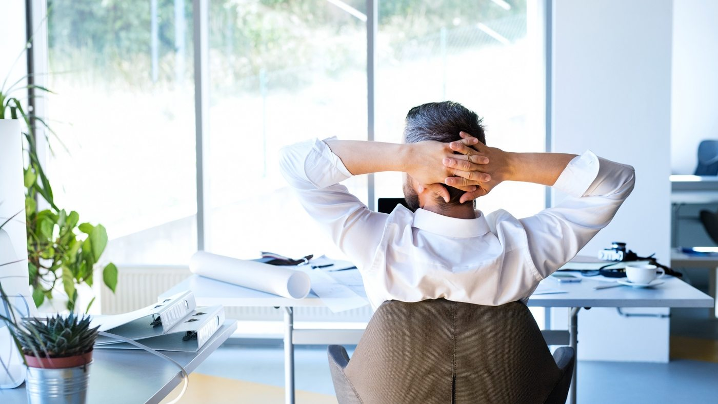 Handsome young businessman in his office, sitting at the desk, stretching arms. Rear view.