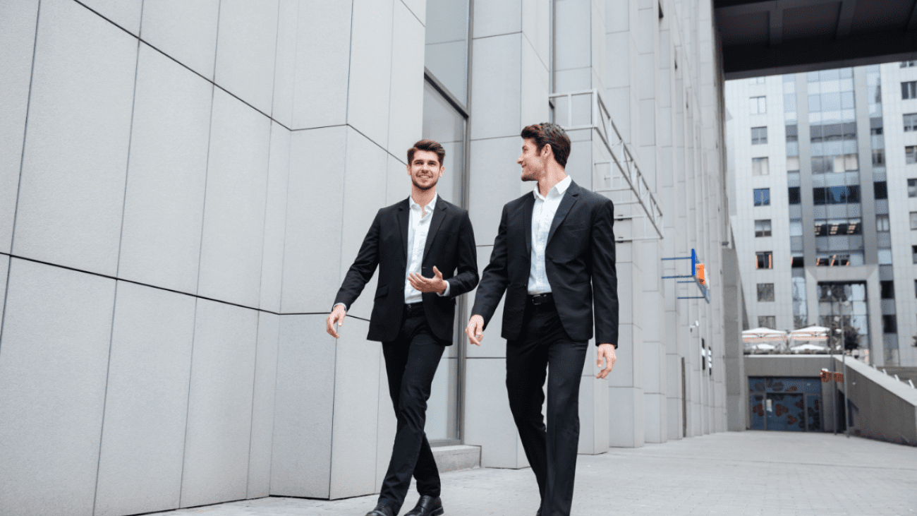 two-businessmen-walking-and-talking-in-the-city-PMW8E26