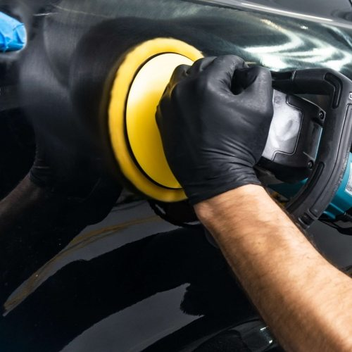Car polish wax worker hands applying protective tape before polishing. Buffing and polishing car. Car detailing. Man holds a polisher in the hand and polishes the car. Tools for polishing