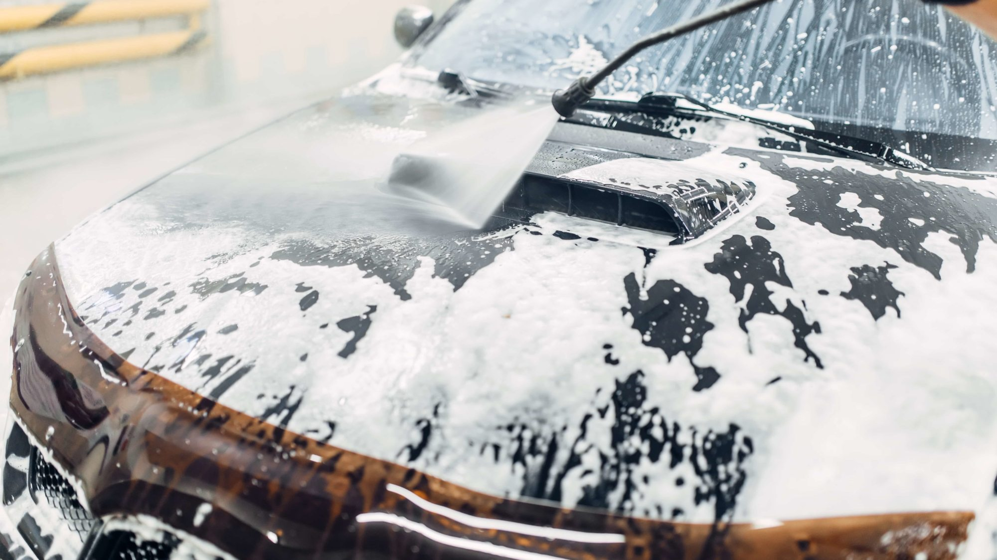 Carwash service, car cleaning, top view on hood. Auto detailing, washing foam off