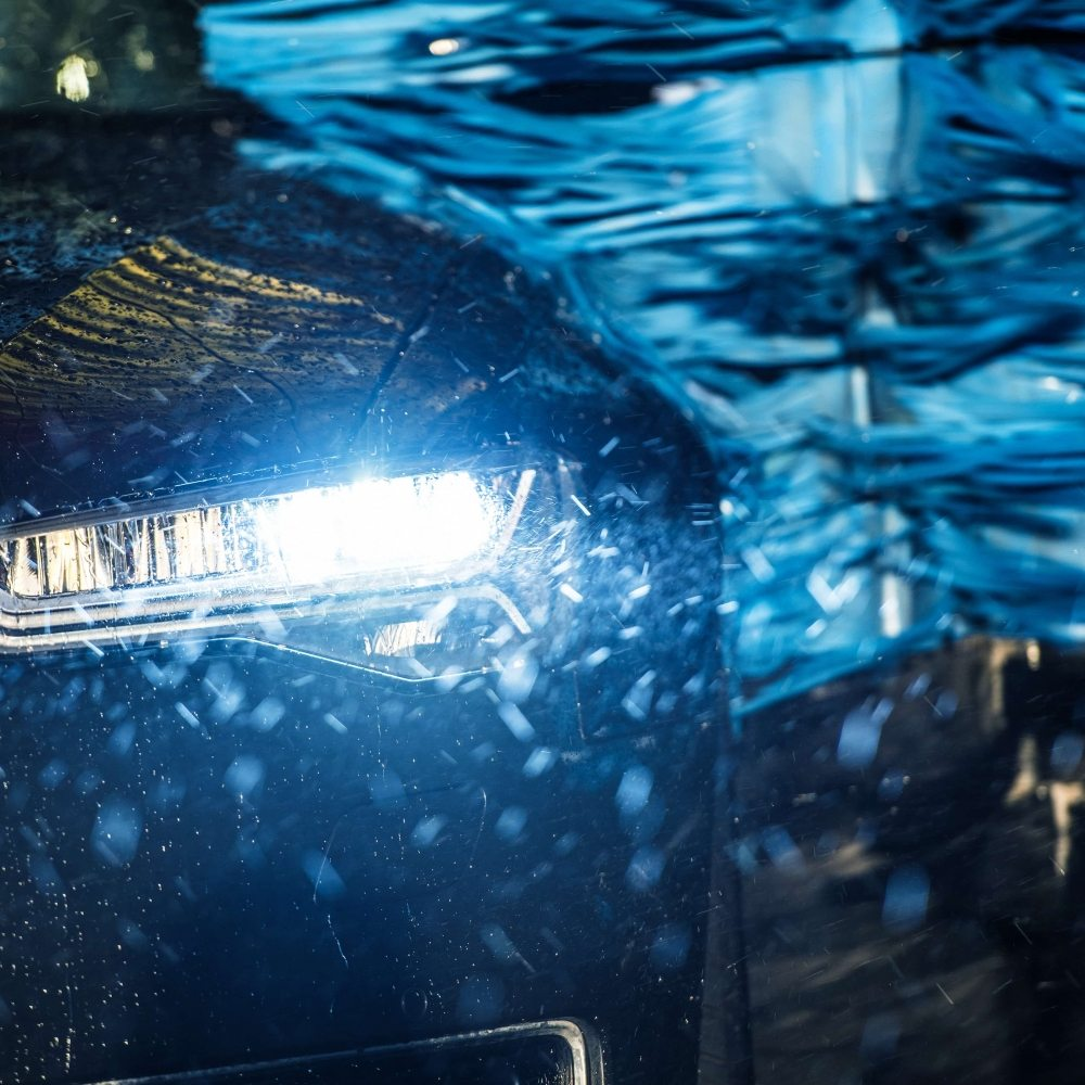 Modern Vehicle in the Automatic Brush Car Wash Closeup Photo.