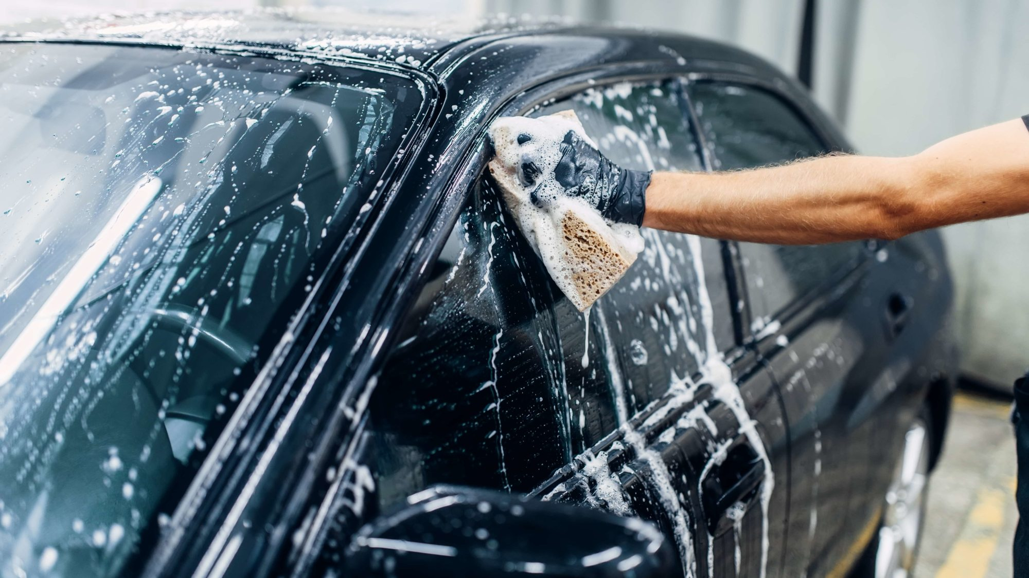 Carwash service, car cleaning, front view. Auto detailing, worker soaps glasses