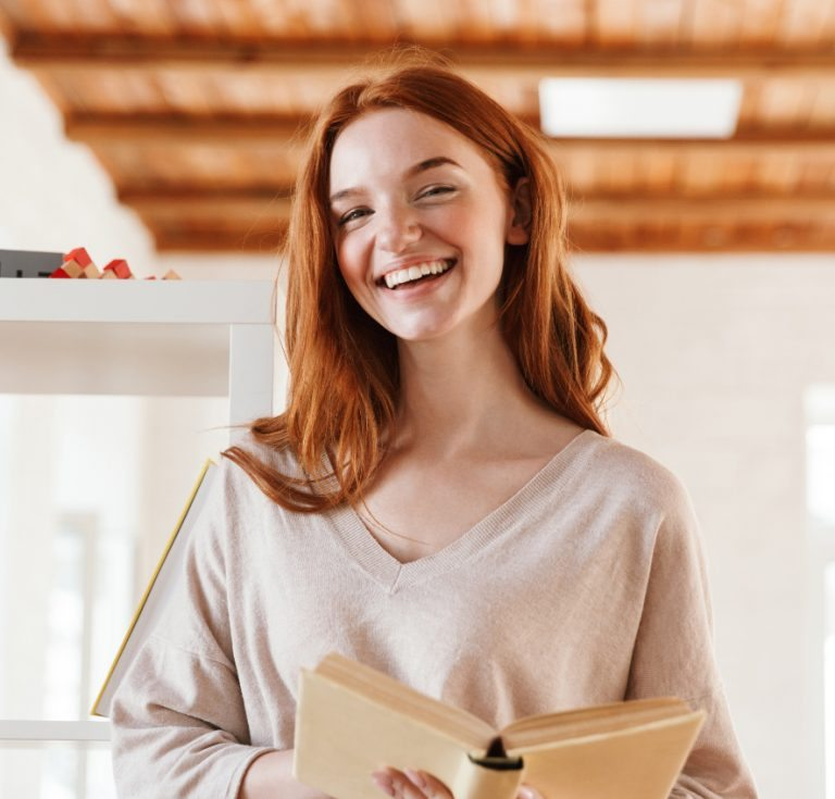 happy-redhead-young-lady-student-reading-book-M5Z7RVC@2x