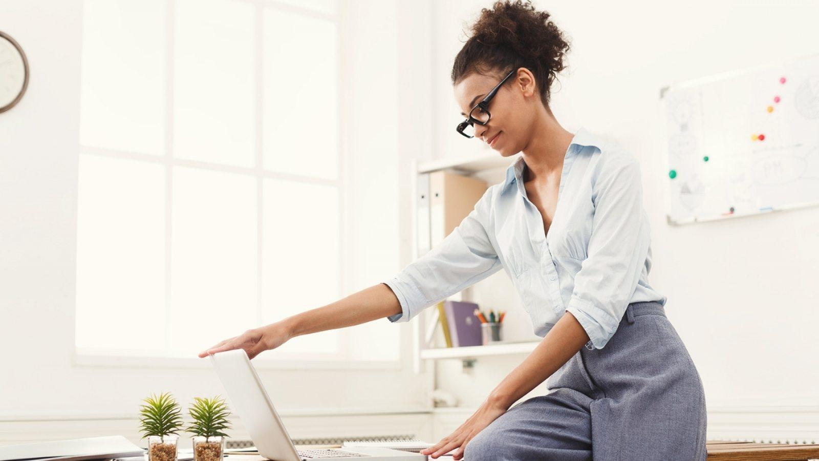 business-woman-opening-laptop-at-office-PU4ZAGW