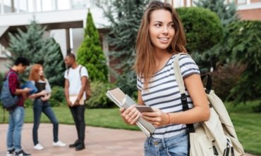 happy-woman-student-with-backpack-holding-books-PNFUGG7(1)