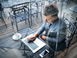 mature-businessman-with-laptop-outside-a-cafe-PXAVBAC