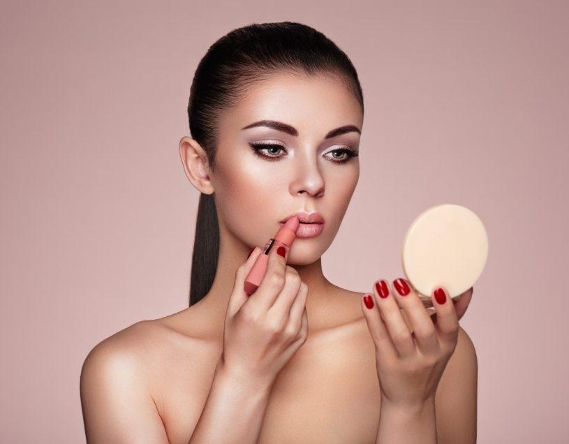 beautiful-woman-paints-lips-with-lipstick-PMB6YWP