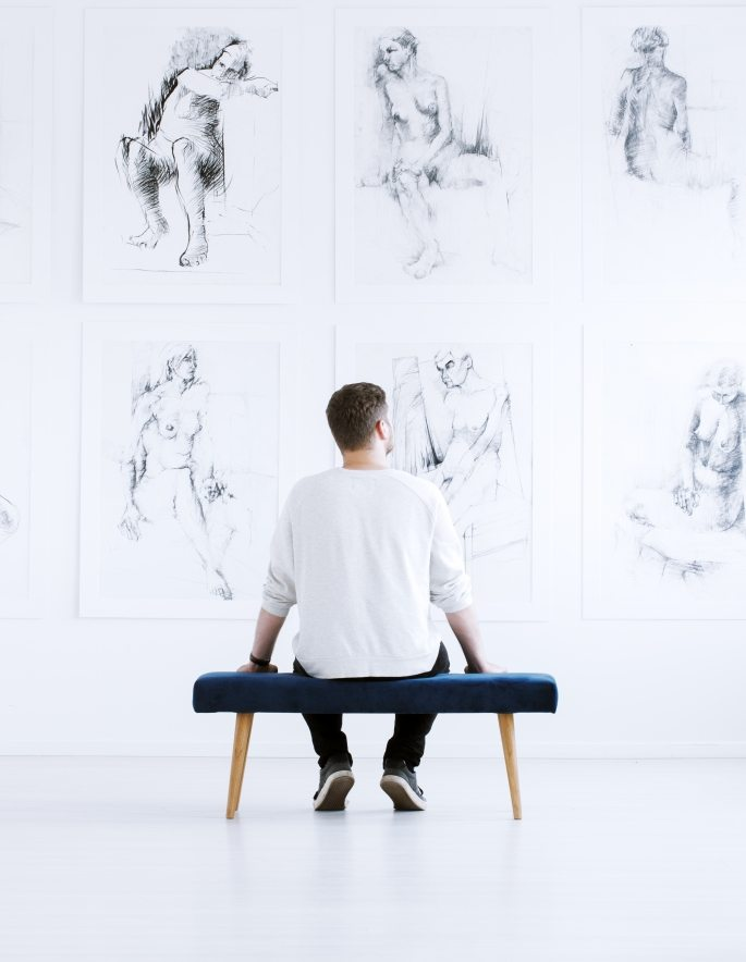 Man relaxing in art gallery while sitting on stool in front of white wall with drawings. Art gallery concept