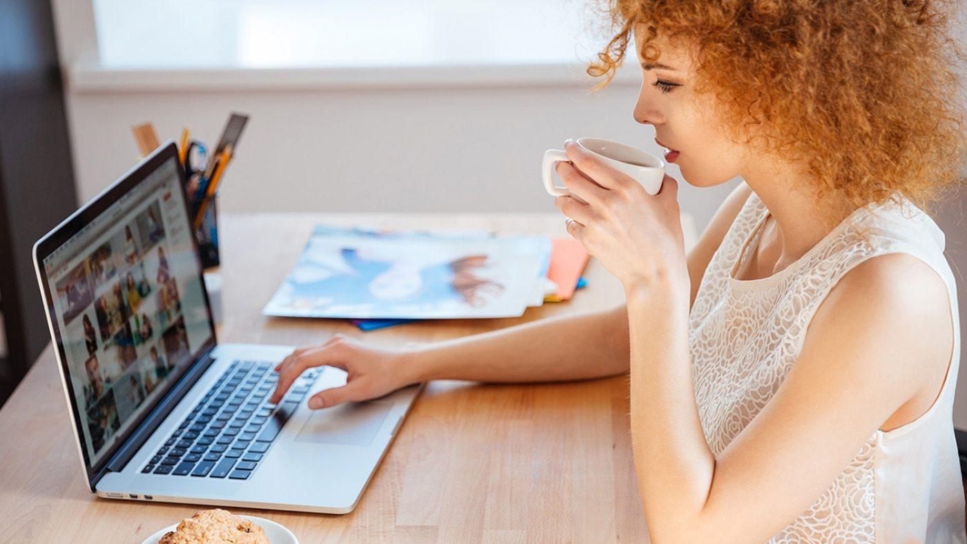 woman-photographer-drinking-coffee-and-working-PJNBP6U
