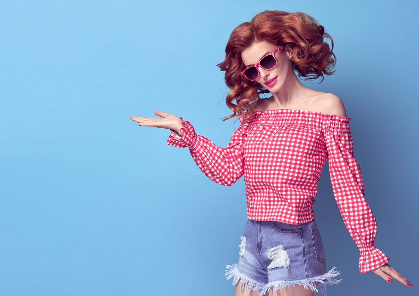 Fashion Pretty PinUp Redhead Girl Smiling Having Fun. Presenting your product. Playful Woman in Pink Summer Bardot Top, Denim shorts, Sunglasses. Trendy Curly hairstyle