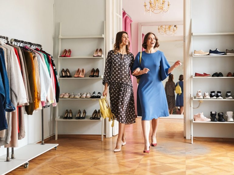 Photo of two pretty young women shopaholics indoors in shop showroom. Looking aside.
