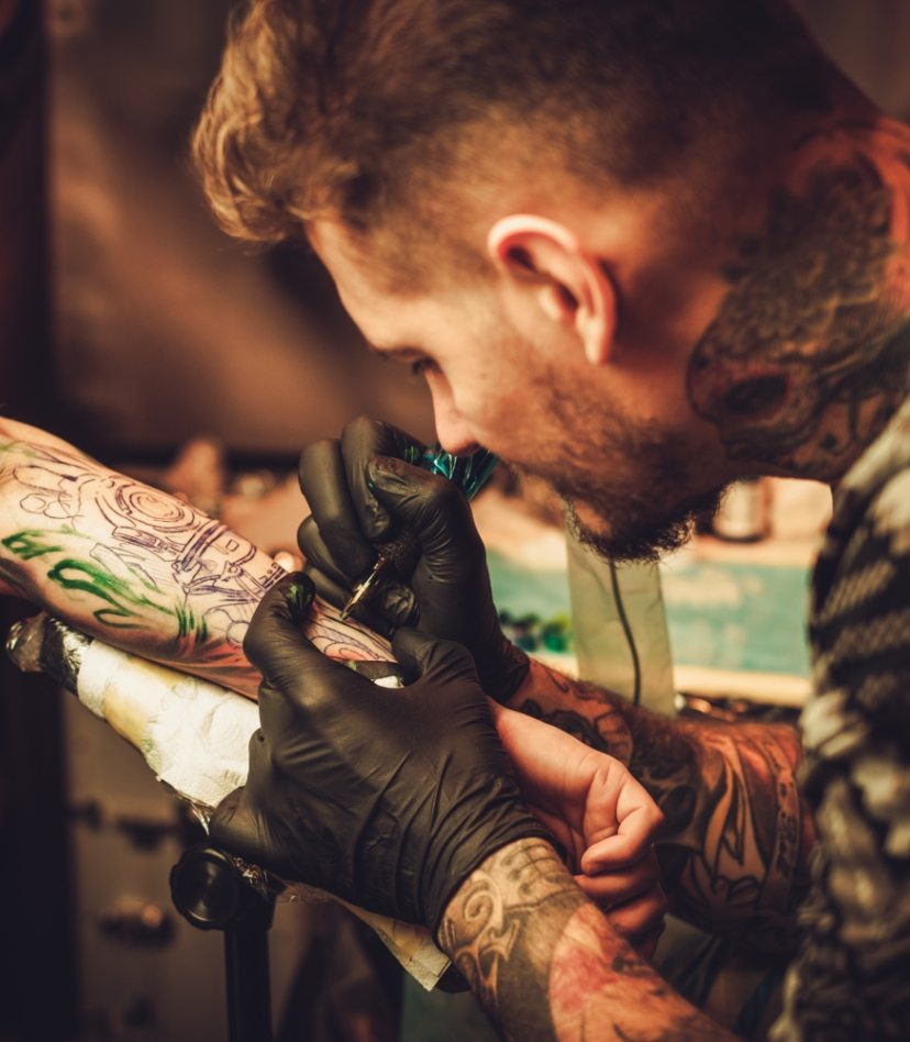 tattoo-artist-makes-a-tattoo-on-a-mans-hand-PECZRE2