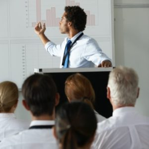 young-businessman-delivering-presentation-at-PF276WZ@2x
